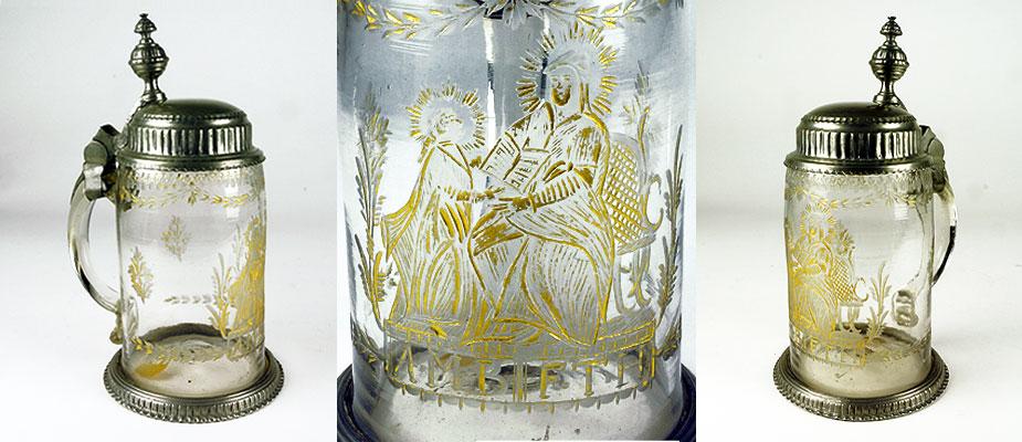 Zylindrischer Gefäßkörper mit geschnittener Darstellung, Hl. Anna lehrt Maria das Lesen. Krug mit Zinndeckel und Standring montiert. Blumengirlanden und Blumensträuße in Kerbschliff. Am Lippenrand Girlande mit Kugelschliffdekor. Über dem Standring ein Schriftband. In den Schliffen Reste von Vergoldung. Henkel breit und flach angesetzt. Maße: H 23 x Durchmesser 10 cm Empire um 1810