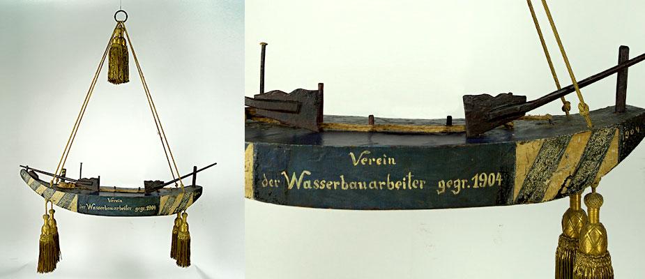 Innplätte in Holz, farbig gefasst. Am Bug und Heck, Ruder mit Seilen. Originale Aufhängung mit Goldquasten und Goldschnüren. 1904 wieder verwendet als Zunftzeichen der königlich bayerischen Wasserbauer in Wasserburg am Inn. Maße: H 100 x B 45 x T 23 cm Wasserburg am Inn um 1750
