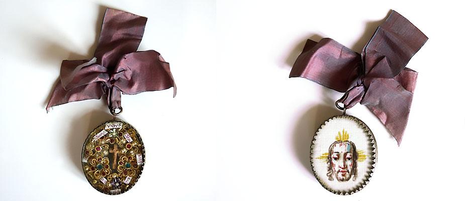 Ovaler Wallfahrtsanhänger, auf der Vorderseite Reliquien mit Spruchbändern in Drahtarbeiten. Im Zentrum kleines geschnitztes Cruzifix aus Birnbaumholz. Rückseitig, Schweistuch der Veronika auf Leinen gemalt. Die Zangenfassung aus Silber mit gedrehtem Silberdraht. Maße: H 5 x B 4 x  1,5 cm Bayern, 18. Jahrhundert