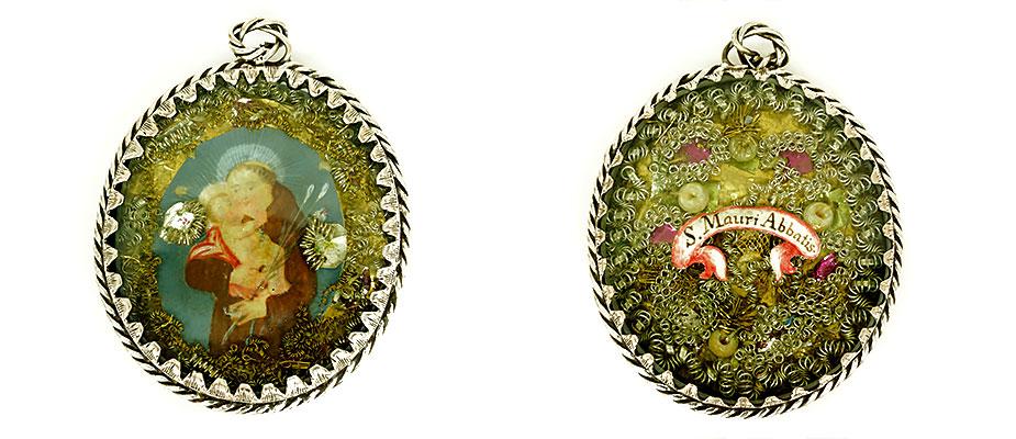 Antoniusanhänger in gravierter Zackenfassung, beidseitig mit Glas verschlossen. Auf der VorderseitePergamentbild mit dem Hl. Antonius, auf der Rückseite Reliquie mit Schriftbanderole, S. Mauri Abbatis und Silberdrahtarbeiten. Maße: H 6,5 x B 5,5 x D 1,2 cm Bayern um 1750