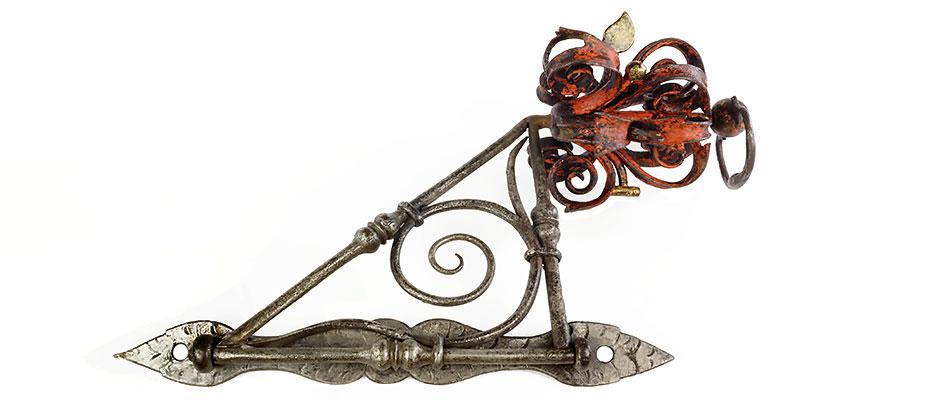 Kleiner Ausleger, vermutlich für die Fixierung eines Seils. Die Befestigungsplatte für die Wand ziseliert und verzinnt wie der Ausleger. Die Auslegerblume verziert mit Werkzeugen, rot bemalt und vergoldet. Maße: H 35 x B 11 x T 21 cm Bayern um 1600